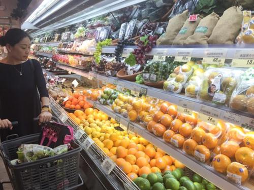 Một khách hàng đang xem hoa quả nhập khẩu tại siêu thị ở Thượng Hải. Ảnh: Nikkei