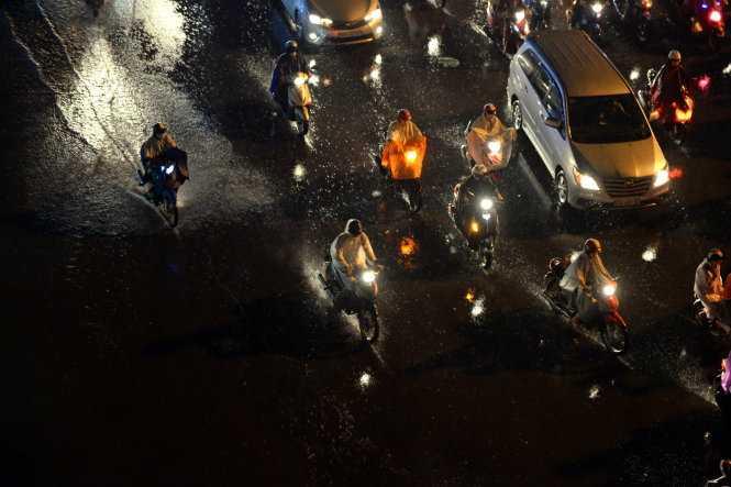 Người dân đội mưa về nhà để tránh kẹt xe - Ảnh: Hữu Khoa
