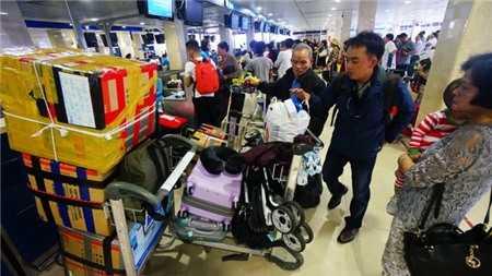 Sân bay Tân Sơn Nhất dịp tết hay quá tải là không tránh khỏi. Nhiều hãng hàng không có nguy cơ không được cấp phép tăng chuyến dù đã bán vé. Trong ảnh: hành khách làm thủ tục lên máy bay tại sân bay Tân Sơn Nhất - Ảnh: Quang Định