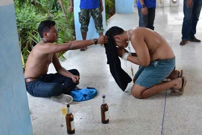 Một đàn em bị trói tay, quỳ lạy đàn anh và phải uống