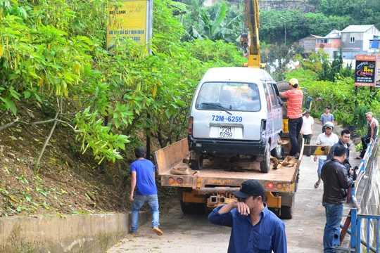 Xe ô tô rơi xuống vực được lực lượng cứu hộ đưa lên trong tình trạng hư hỏng nặng phần đầu.