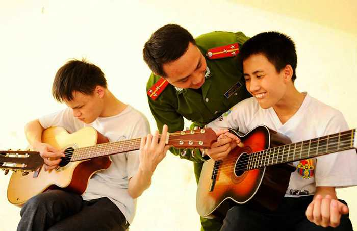 Hinh anh Nguong mo thay giao cong an day guitar cho tre em khiem thi