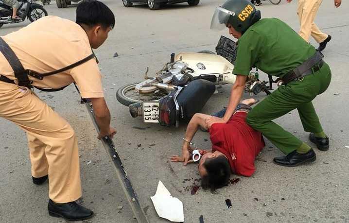 Tên cướp bị bắt khi liều vượt đèn đỏ, đâm vào xe ô tô, ngã xuống đường. Ảnh: Thanh Loan.