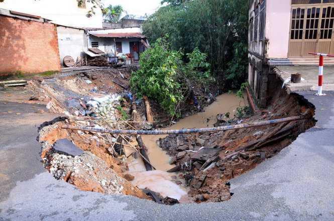 Một khoảng rộng hàng chục mét vuông, hàng tấn đất, đá, nhựa đường bị sạt lở, đổ xuống suối - Ảnh: A LỘC