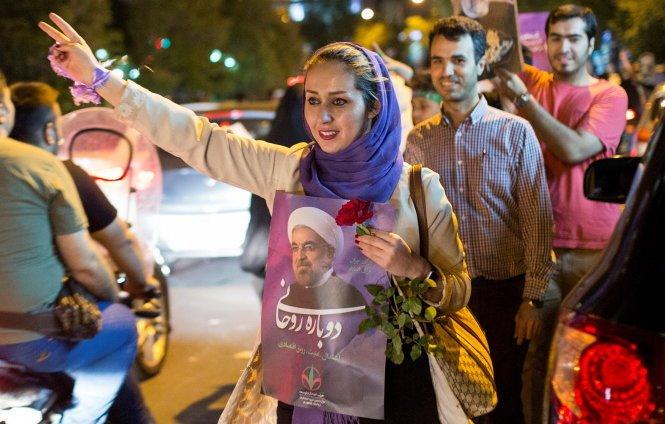 Cử tri ủng hộ ứng viên Hassan Rouhani mang hình ảnh ông trong cuộc tuần hành trên đường phố ở Tehran - Ảnh: Reuters