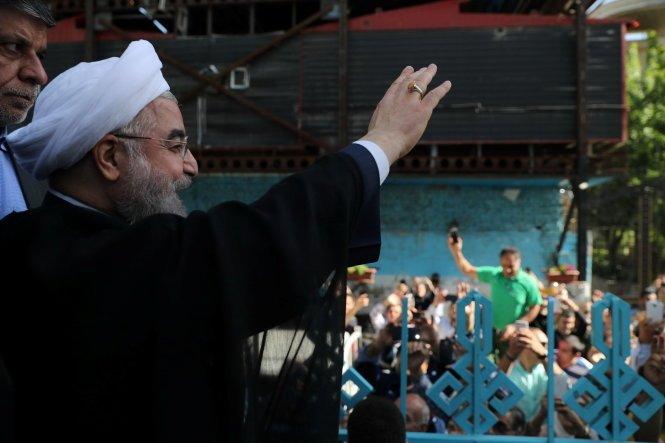 Ứng viên đương kim tổng thống Hassan Rouhani vẫy chào người ủng hộ sau khi ông bỏ phiếu ở thủ đô Tehran ngày 19-5 - Ảnh: Reuters