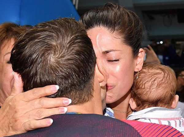 Sau khi đoạt tấm HC vàng 200m bơi bướm hôm 9/8,Michael Phelps tiến tới khán đài nơi vợ con anh đứng để chia vui. Kỷ lục gia Olympic hạnh phúc khóa môi bà xã trong tiếng hò reo của mọi người xung quanh.