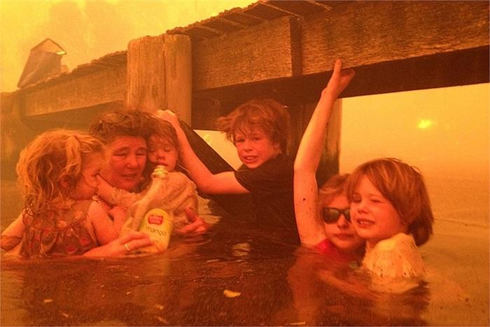 Bà Tammy Holmes và đàn cháu nương náu dưới một cầu cảng trong vụ cháy rừng ở thị trấn Dunalley, Úc