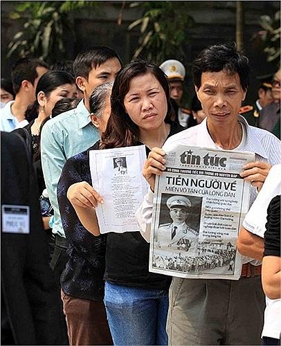 Người dân mang theo những bài báo xúc động khi đến viếng Đại tướng tại Hà Nội. Ảnh: Quang Minh