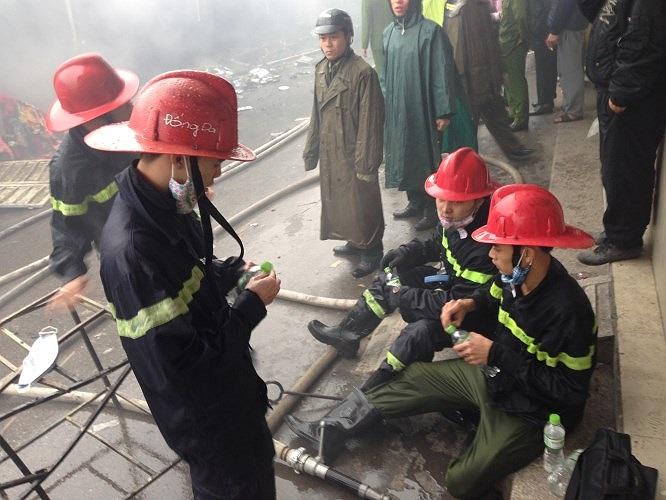 Lính cứu hỏa nghỉ ngơi sau nhiều tiếng đồng hồ chữa cháy.