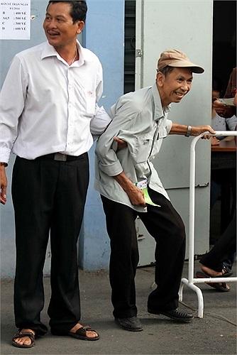 Ông Phạm Văn Nghị (phải), 74 tuổi đạp xe từ quận 8 sang sân Thống Nhất để mua vé (Ảnh: Thanh Niên)