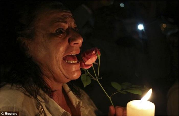 Một phụ nữ Nam Phi cầm hoa tỏ lòng thành kính trước sự ra đi của cố tổng thống
