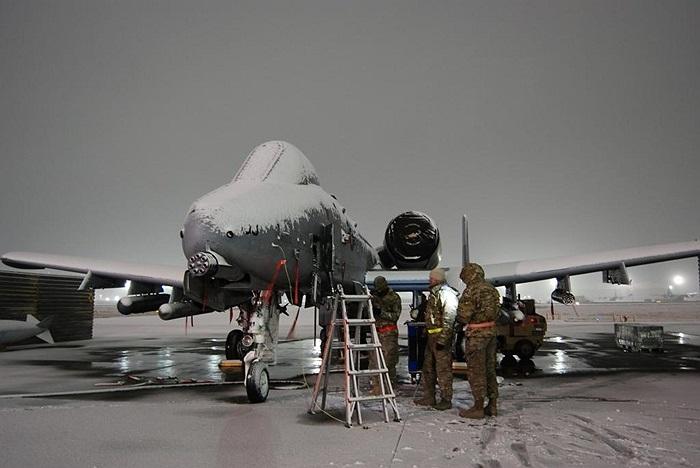 Các binh sĩ đang dọn dẹp tuyết bao phủ trên chiến cơ A-10 Thunderbolt II