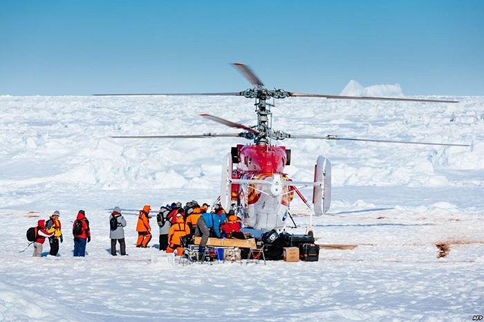 Máy bay trực thăng từ chiếc tàu phá băng Xue Long của Trung Quốc đón hành khách đầu tiên từ chiếc tàu MV Akademik Shokalskiy của Nga bị kẹt ở Nam cực