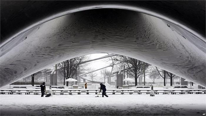 Nhân viên công viên dọn tuyết quanh tác phẩm điêu khắc bằng thép Cổng Mây của điêu khắc gia Annish Kapoor tại Công viên Milllenium, Mỹ