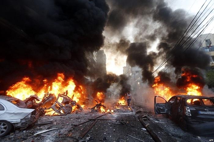 Lửa bốc lên từ những chiếc xe bị cháy nơi xảy ra vụ nổ xe cài bom ở ngoại ô Haret Hreik của thủ đô Beirut, Lebon