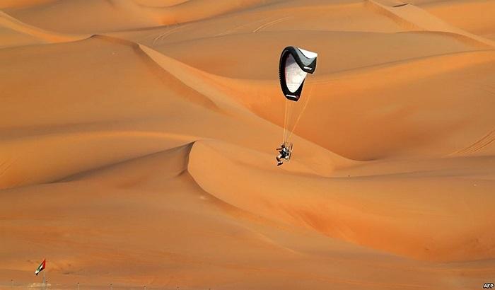 Phi công trên chiếc dù bay, bay phía trên các đụn cát của sa mạc Liwa, UAE