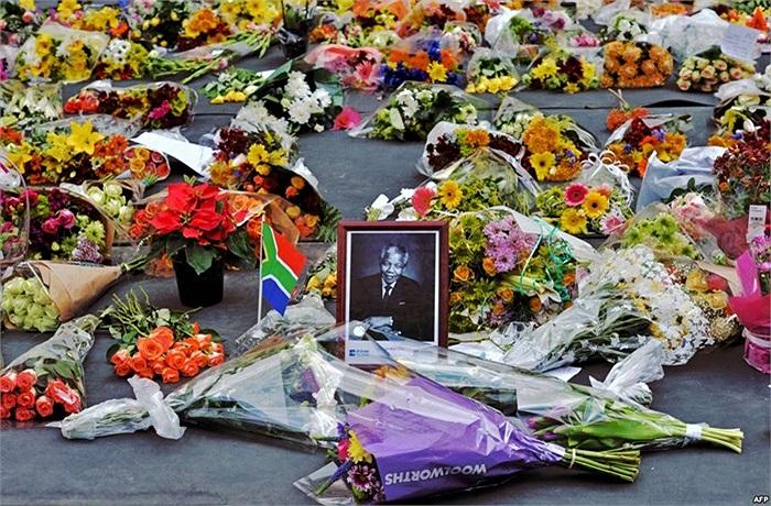 Ảnh ông Nelson Mandela giữa những bó hoa của những người thương tiếc sự ra đi của ông, khu Sandton, thành phố Johannesburg, Nam Phi