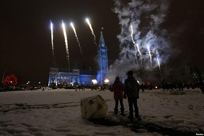 Trẻ em xem pháo hoa trong một buổi lễ thắp sáng mừng Giáng sinh ở Parliament Hill, thủ đô Ottawa, Canada