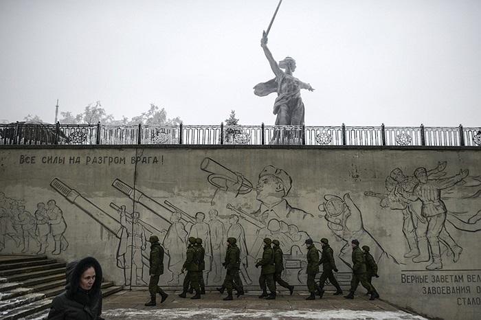 Các binh sĩ quân đội di chuyển cạnh bức tượng ở Volgograd, Nga