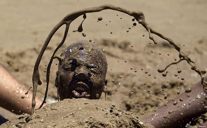Một người tắm cát khi hàng ngàn người ra bãi biển vào ngày đầu năm ở Durban, Nam Phi