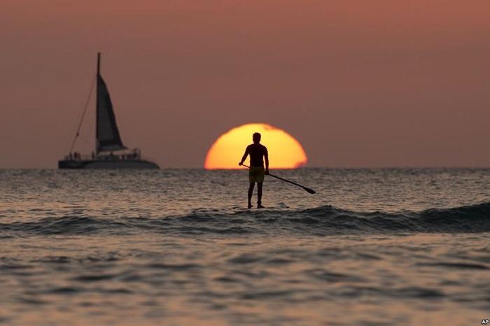 Người đàn ông đứng ngắm mặt trời lặn tại Thái Bình Dương bên ngoài bãi biển Waikiki ở Honolulu