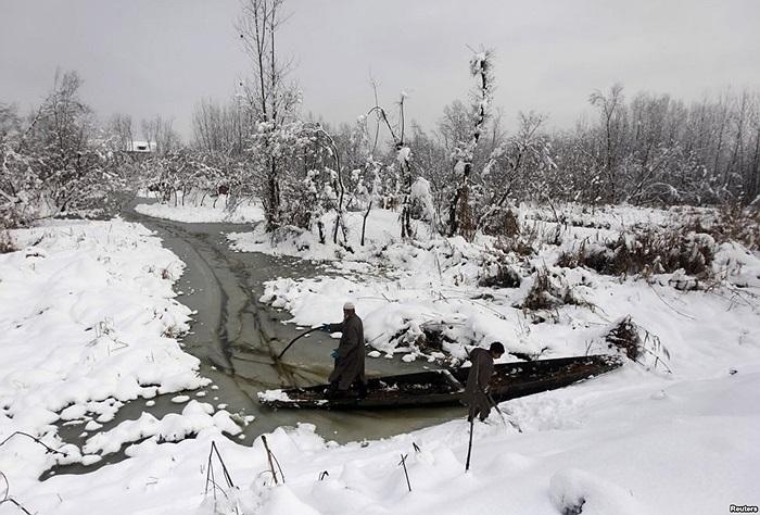 Người Kasmir tìm cách đẩy thuyền của họ qua các giòng nước tại Hồ Anchar sau khi tuyết rơi tại Srinagar, Ấn Độ