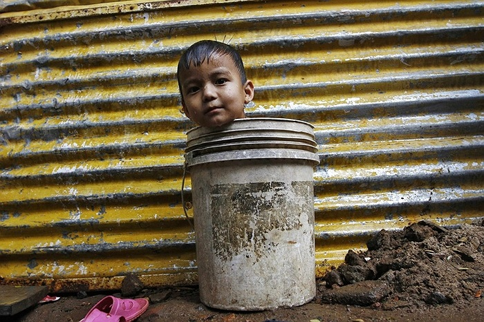 Cậu bé ngồi trong xô nước ở Chennai, Ấn Độ