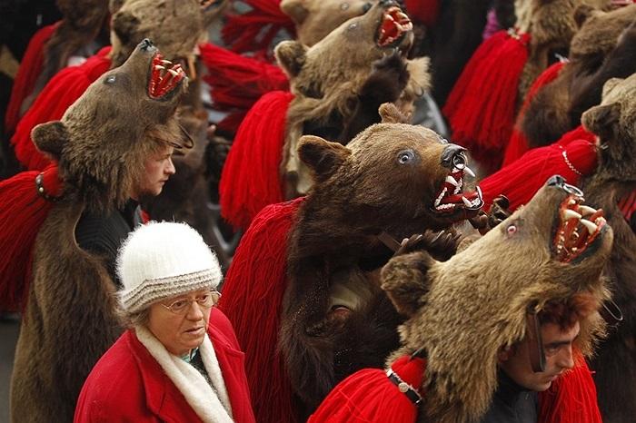 Phụ nữ đội mũ gấu chuẩn bị đón năm mới ở Comanesti, Romani
