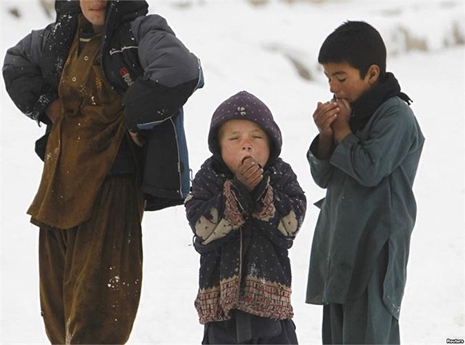 Trẻ em đứng bên ngoài nơi trú ngụ trong thủ đô Kabul, Afghanistan trong một ngày tuyết lạnh giá
