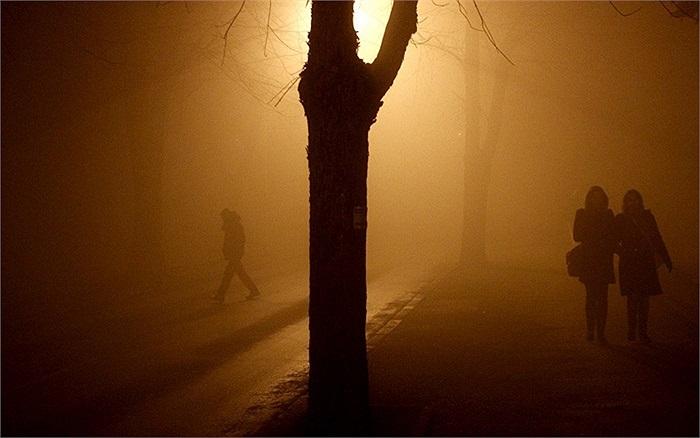 Những người dân đi bộ dưới đường đầy sương khói ở Bosnia