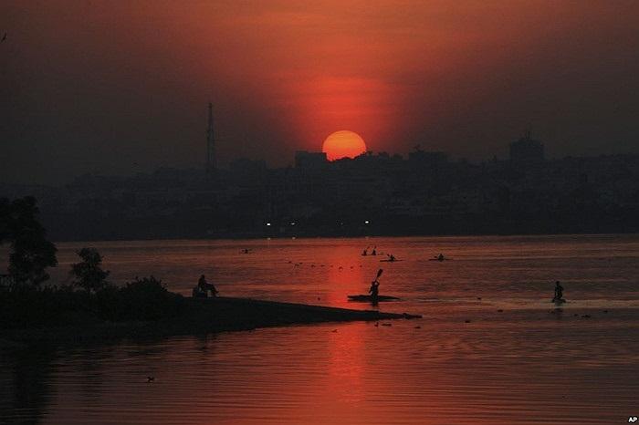 Vận động viên của Ấn Độ quay vào bờ sau khi tập luyện bơi thuyền lúc hoàng hôn trên Hồ Hussain Sagar ở Hyderabad, Ấn Độ