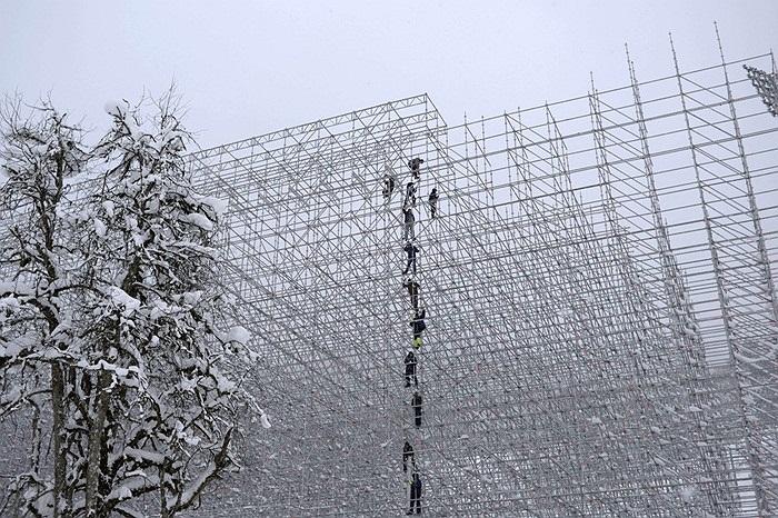 Các công nhân xây dựng đang lắp đặt khán đài một sân vận động của Thế vận hội Sochi 2014 tại Nga trong thời tiết tuyết rơi dày