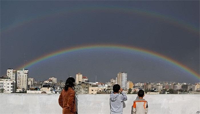 Trẻ em Palestine nhìn cầu vồng tỏa sáng trên những tòa nhà sau mưa lớn ở thành phố Gaza, Gaza