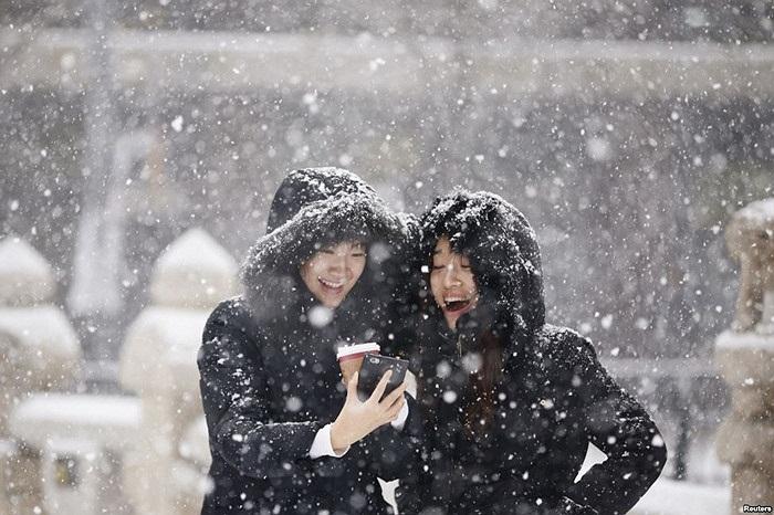 Hai cô gái vui cười khi xem ảnh trên một điện thoại di động giữa lúc tuyết rơi tại trung tâm Seoul, Hàn Quốc