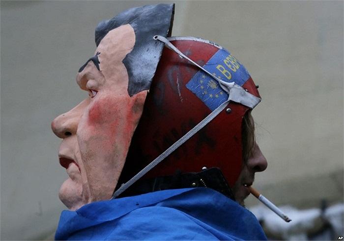 Người biểu tình đeo mặt nạ Tổng thống Viktor Yanukovych khi biểu tình ở thủ đô Kiev, Ukraine