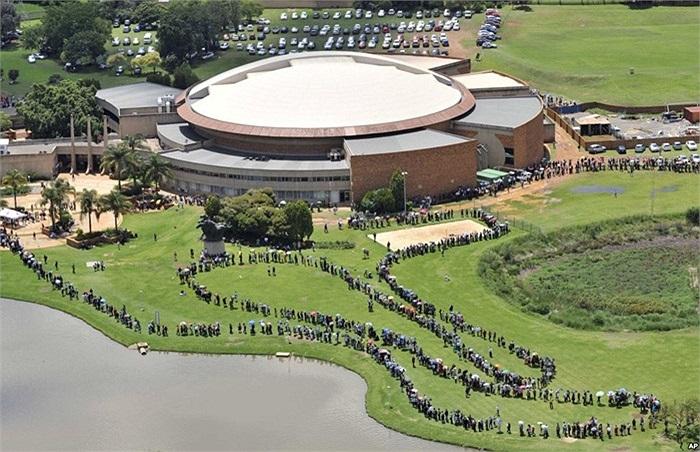 Dân chúng xếp hàng chờ xe buýt trước khi đi tới Union Building ở Pretoria, Nam Phi, nơi đặt linh cữu cố Tổng thống Nelson Mandela