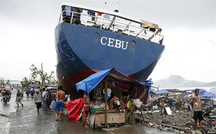 Sạp bán hàng tạm bợ dựng bên cạnh một con tàu bị Siêu bão Haiyan đánh dạt vào bờ hồi tháng trước, tại thành phố Tacloban, miền trung Philippines
