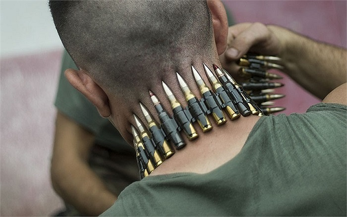 Một người lính Pháp quấn băng đạn quanh cổ trong lúc xử lý kho đạn dược ở nhà ga Bessengue, Douala, Cameroon