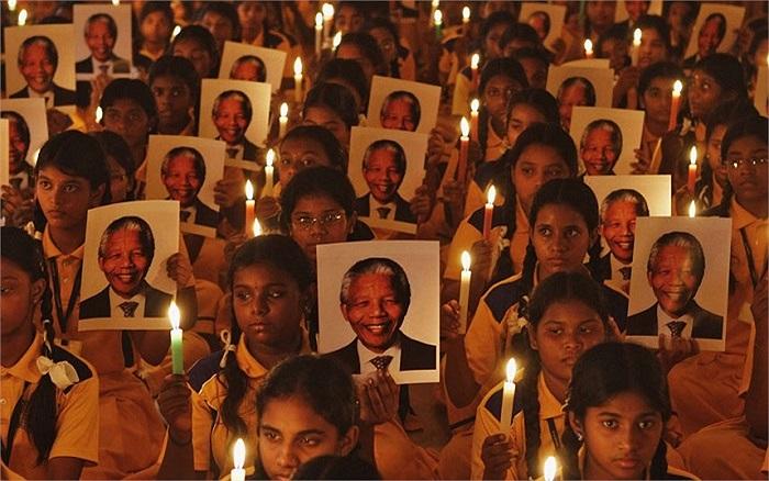 Học sinh Ấn Độ cầm nến và chân dung cố Tổng thống Nelson Mandela trong một buổi lễ cầu nguyện tại trường học