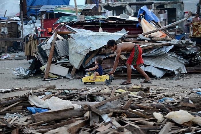 Hai cho con ở Tacloban, Philippines chơi đùa giữa đống đổ nát sau trận siêu bão Haiyan