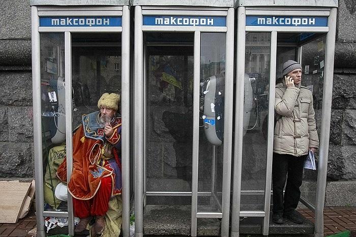 Một người đàn ông mặc đồ truyền thống của Ukraine ngồi hút thuốc trong buồng điện thoại công cộng