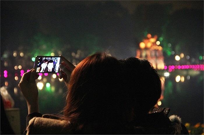 Bên Tháp Rùa rực rỡ ánh đèn, đôi bạn trẻ Hà Thành ghi lại những khoảnh khắc đáng nhớ