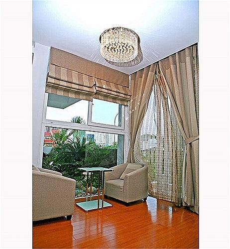 Một góc phòng ngủ với ghế sofa vuông dùng để cà phê sáng vì có thể nhìn ra ngoài khoảng lan can đầy hoa lá.