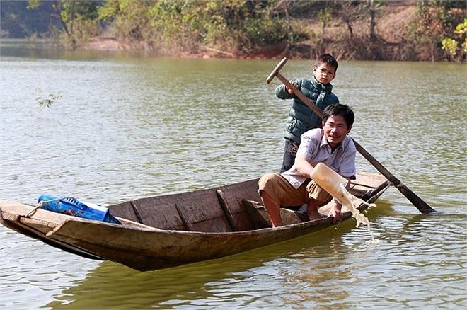 Em Đạt đi học về được bố đón, hai bố con thay nhau chèo, tát nước ra khỏi thuyền.
