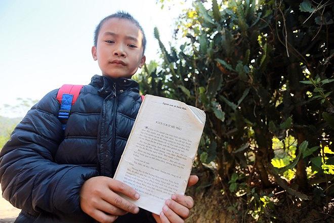Vi Văn Huy với cuốn truyện nhặt được trên tay. Huy cho biết em rất thích cuốn truyện 'Người con út hiếu thảo'