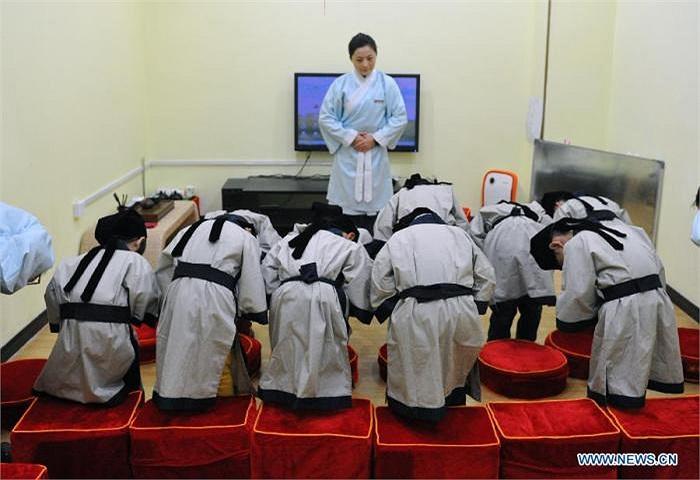 Hình ảnh các em học sinh đang được dạy cách cúi chào những người lớn tuổi hơn mình.