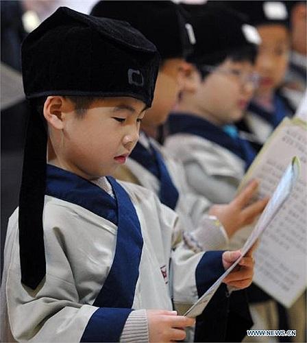 Bé trai chăm chú nhìn vào tập sách được cô giáo phát trong lớp.