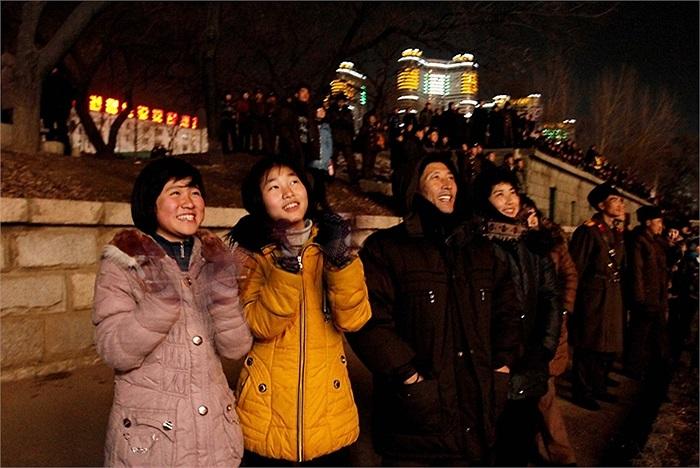 Người dân và các binh sĩ đứng dọc theo bờ sông để ngắm nhìn pháo hoa, xa xa là những tòa cao ốc sáng đèn