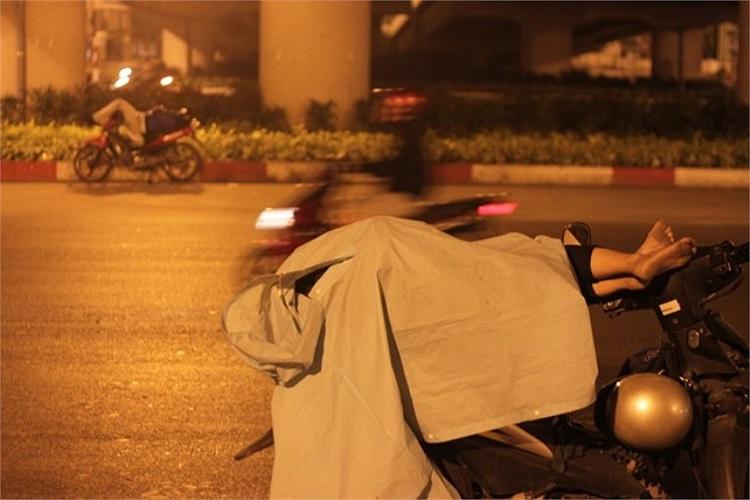Tại ngã tư Bình Triệu, người lái xe ôm trùm áo mưa kín mít.